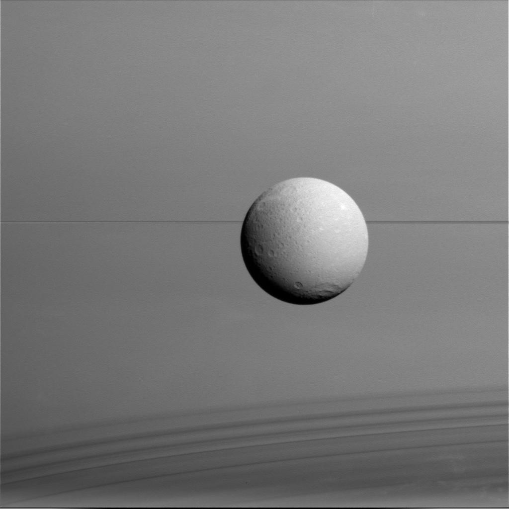 Dione hangs in front of Saturn and its icy rings in this view, captured during Cassini's final close flyby of the icy moon.