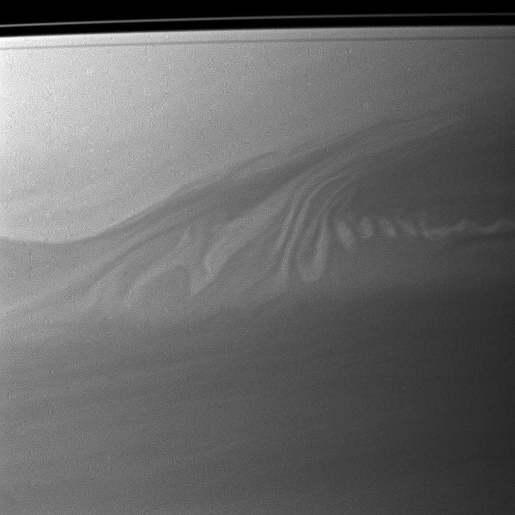 Clouds in Saturn's atmosphere create an intricate pattern reminiscent of whipped cream swirling in coffee.