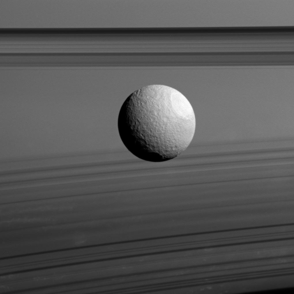 Black and white image of Saturn's moon Tethys in front of Saturn's rings.