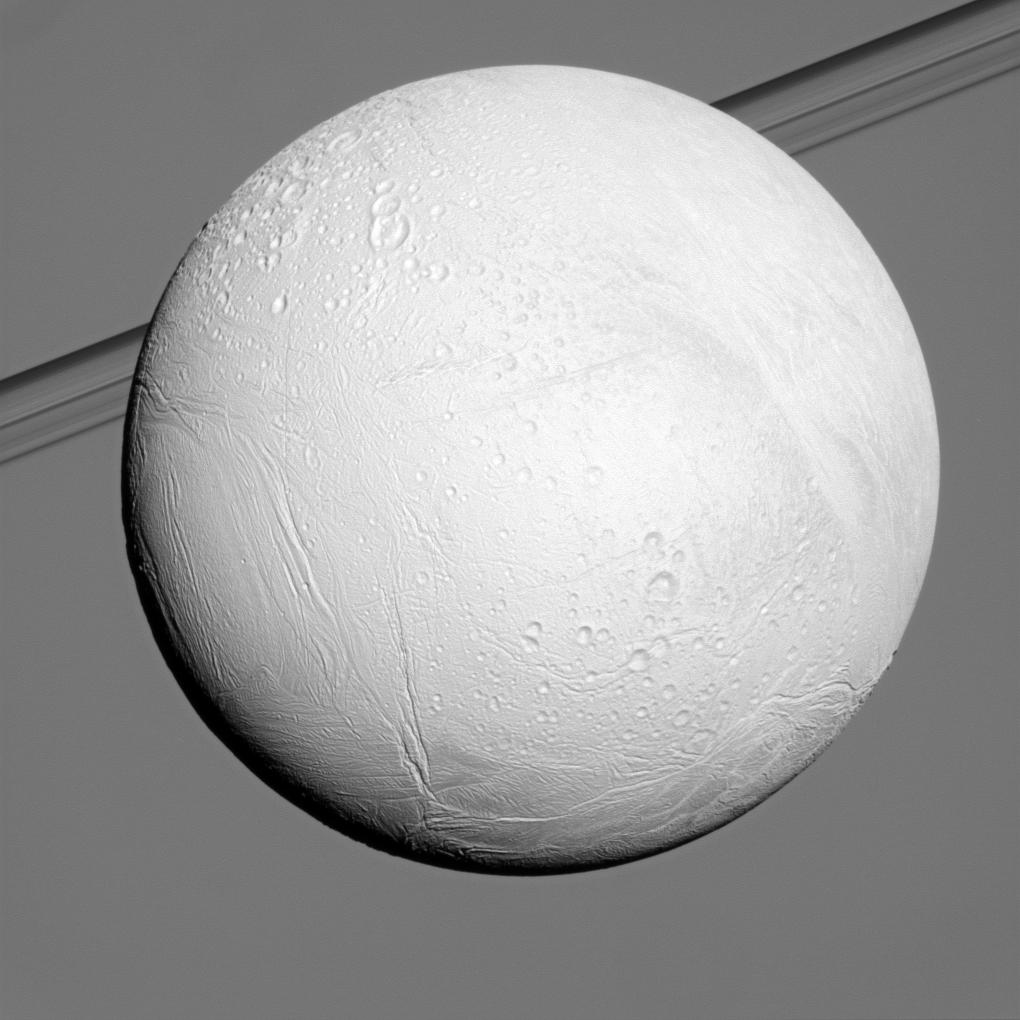 Saturn's moon Enceladus reflects sunlight brightly while the planet and its rings fill the background of this Cassini view.
