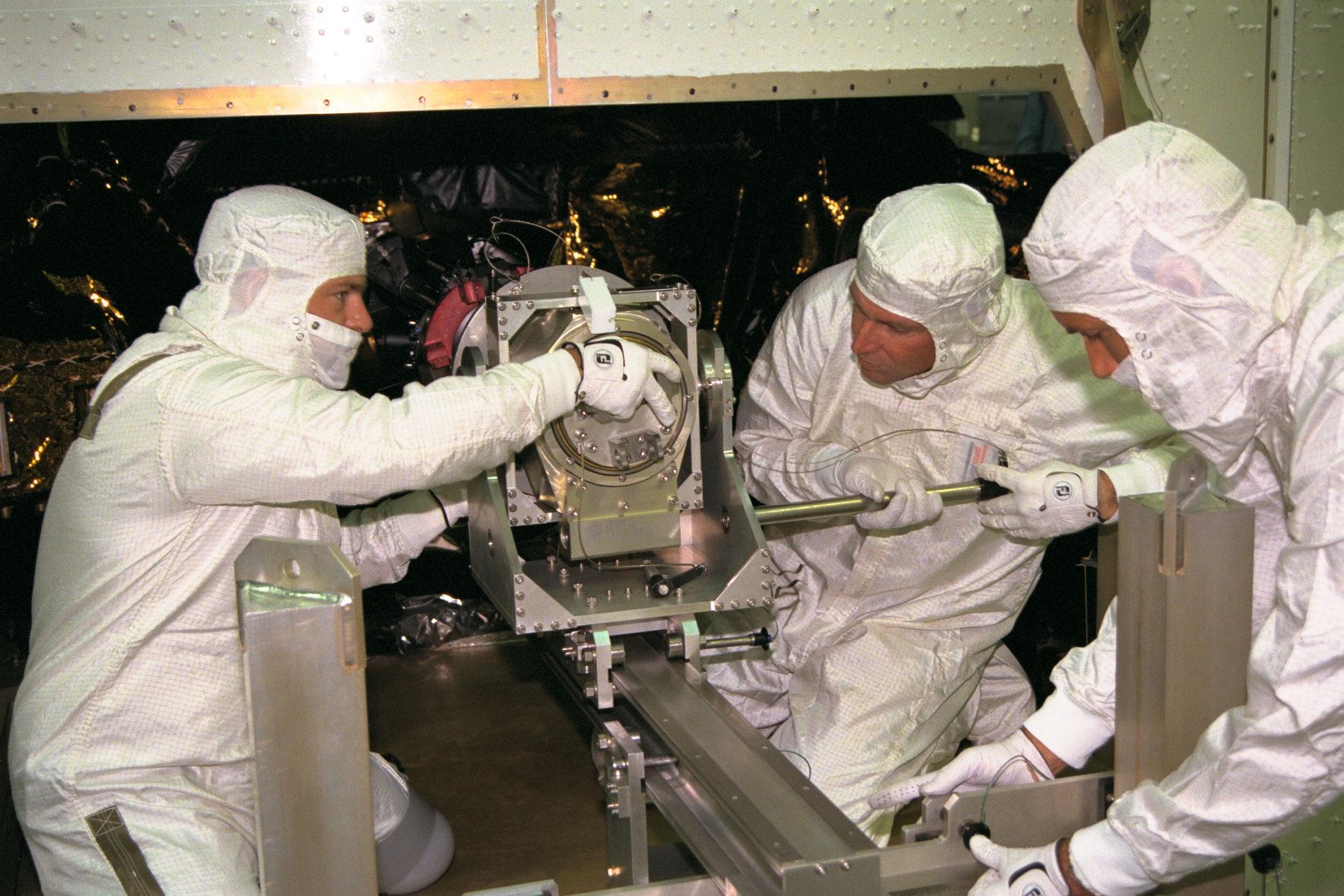 Three men install parts on a spacecraft.