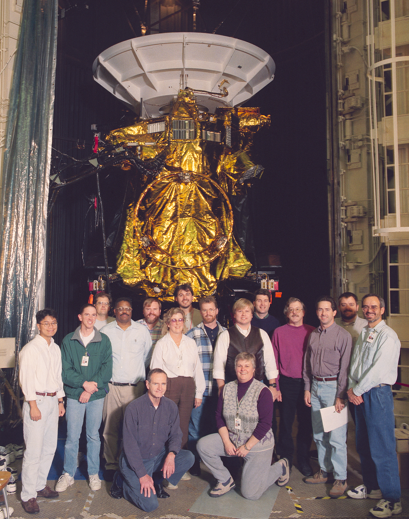 Group of people in front of spacecraft.