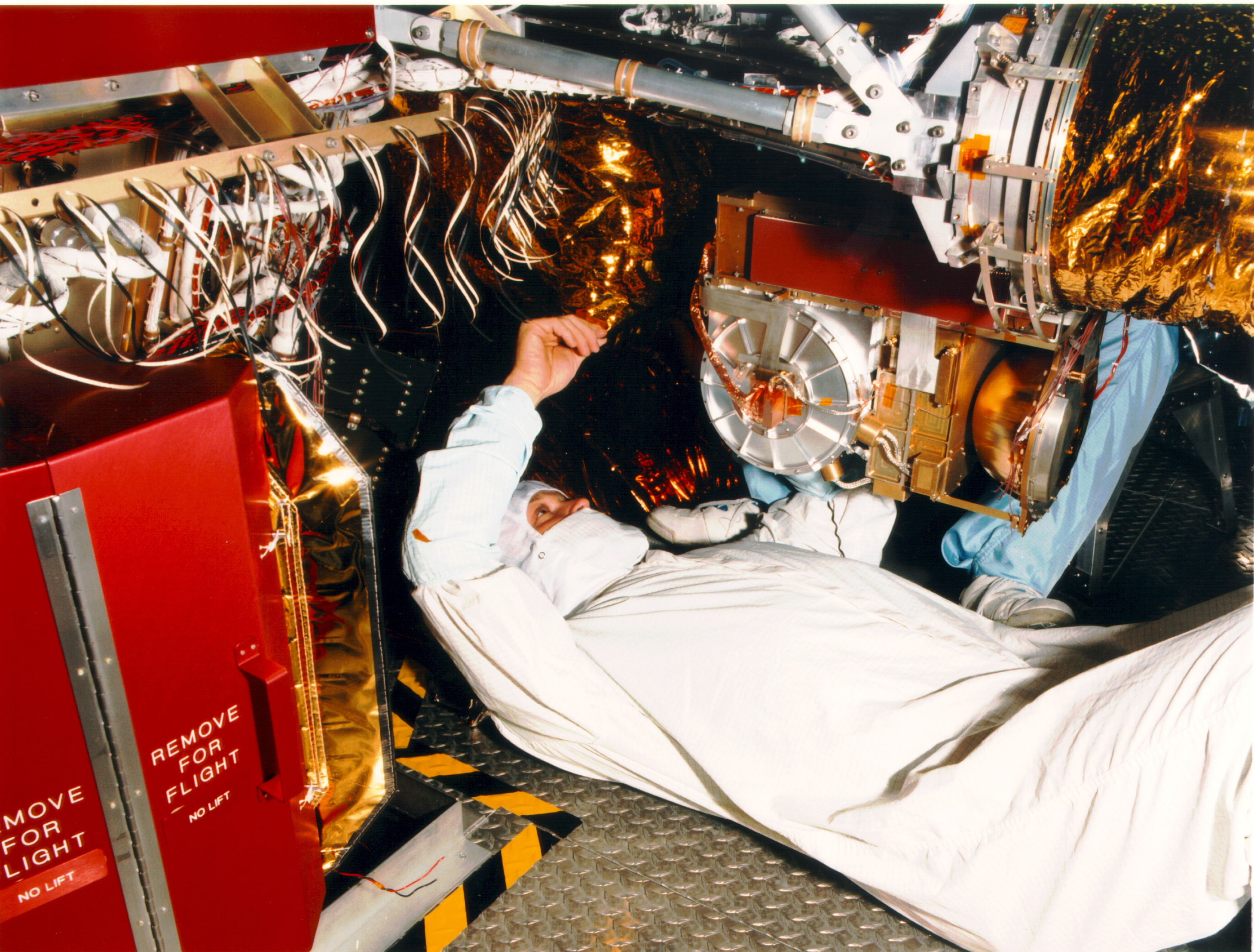 Color image of man on his back working on a spacecraft.