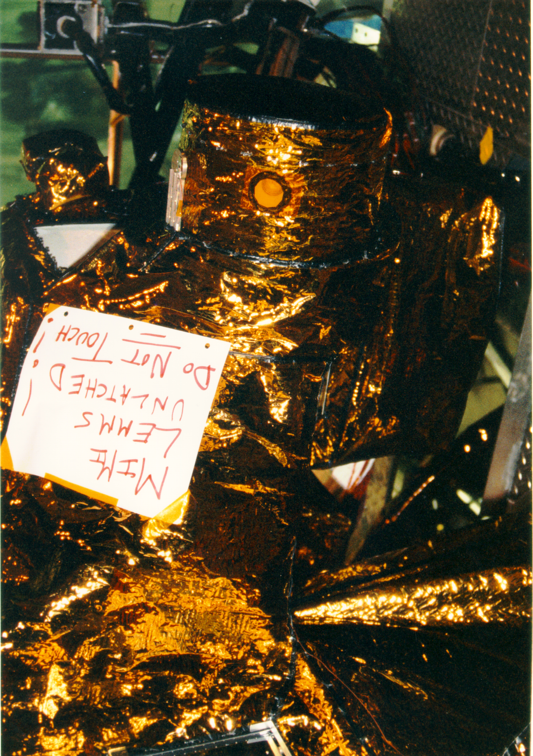 "Color image of spacecraft with a note on it that says ""MIMI LEMMS unlatched! Do not touch!"""