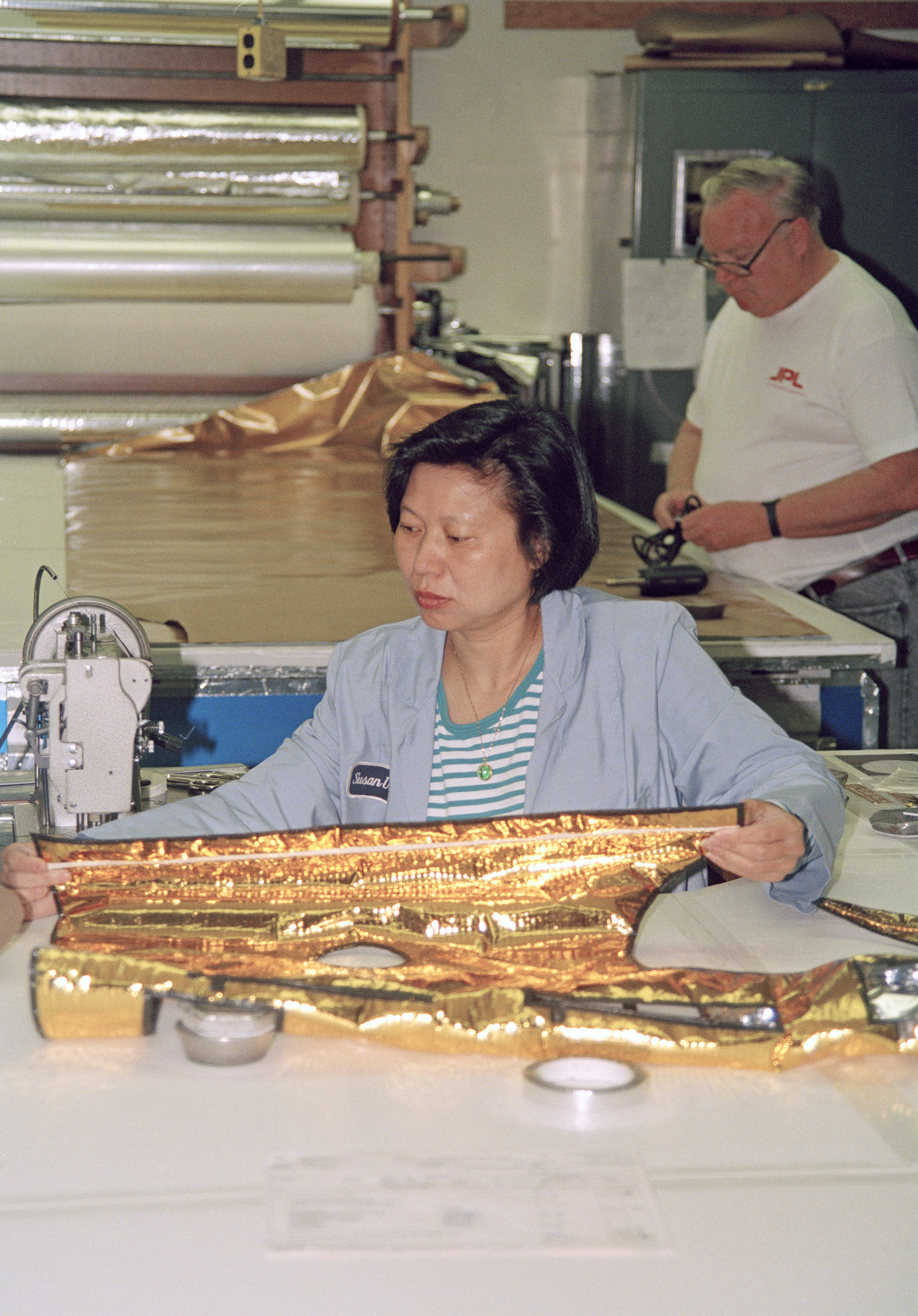 Color image of woman sewing a gold-colored thermal spacecraft blanket.