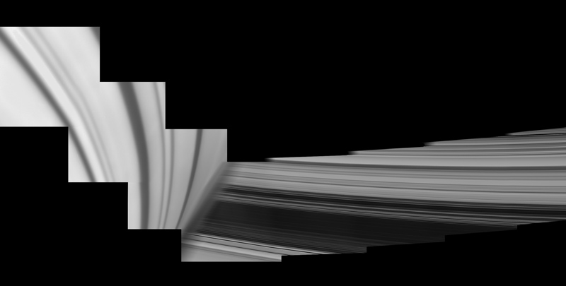 Saturn's rings emerge from behind the planet's hazy limb