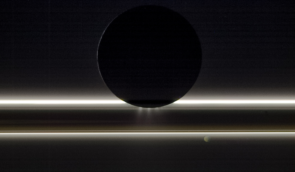 A backlit view of Enceladus and Saturn's rings
