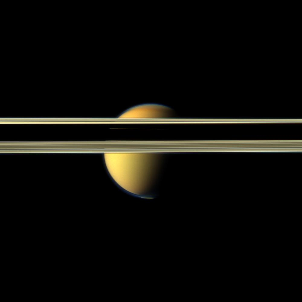 Saturn's rings obscure part of Titan's colorful visage in this image from NASA's Cassini spacecraft.