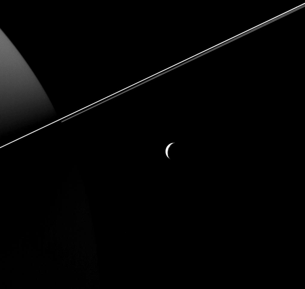 Tethys, dwarfed by the scale of Saturn and its rings, appears as an elegant crescent in this image taken by NASA's Cassini Spacecraft.