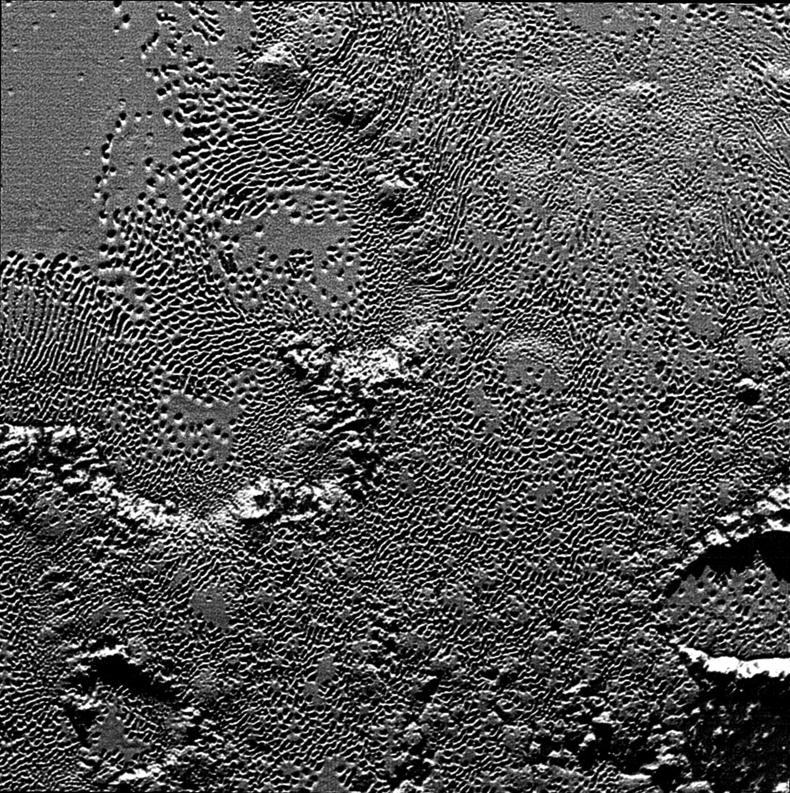 "On July 14 the telescopic camera on NASA's New Horizons spacecraft took the highest resolution images ever obtained of the intricate pattern of ""pits"" across a section of Pluto's prominent heart-shaped region, informally named Tombaugh Regio."