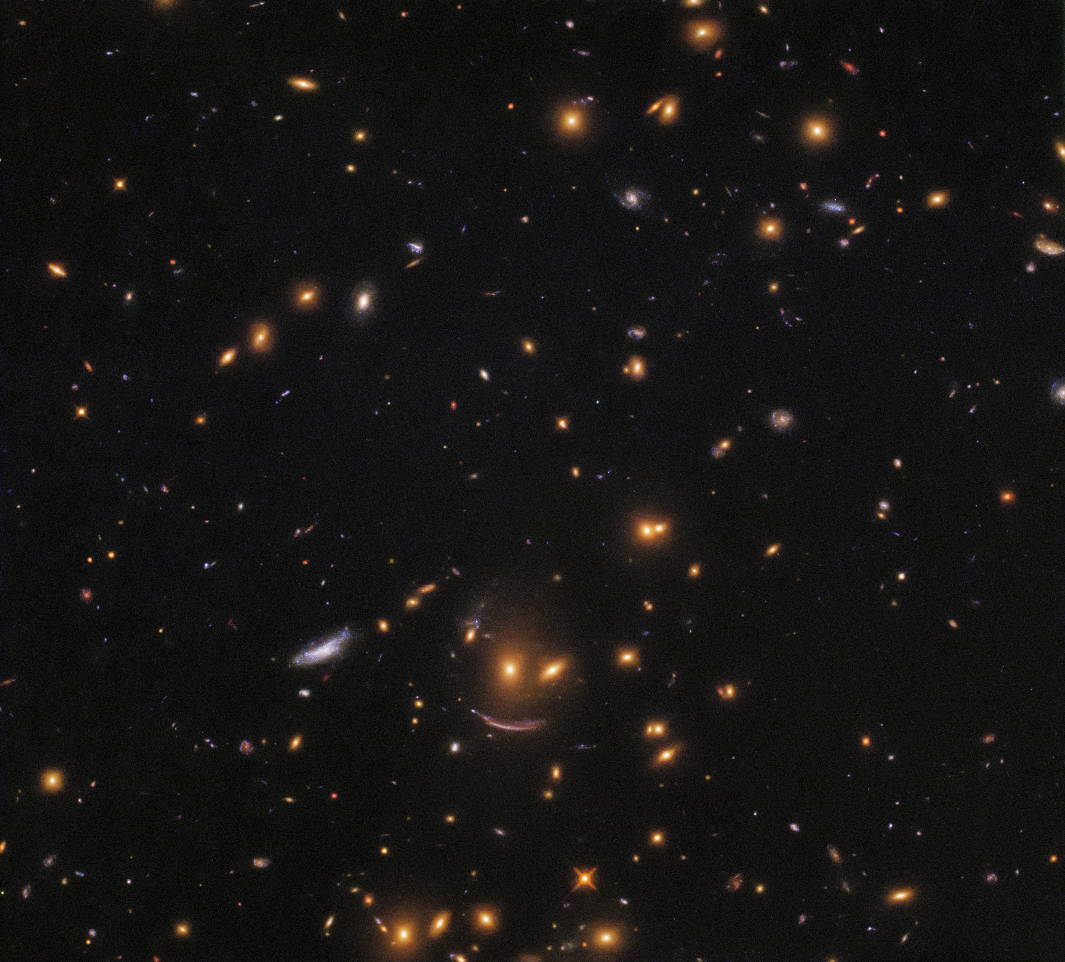 Collection of galaxies including a trio that form in the shape of a classic cartoon smiley face-- two dots for eyes and a curved line for a mouth.