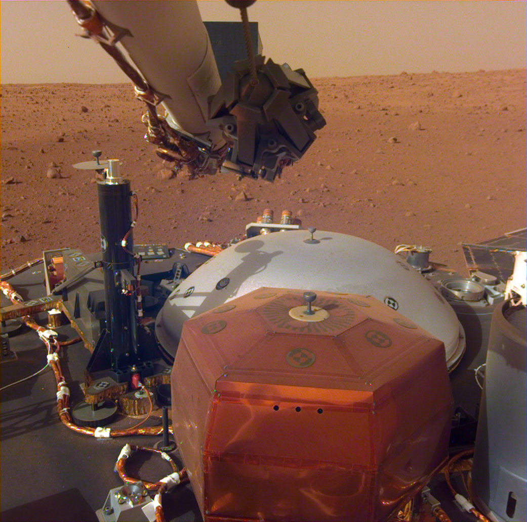 Spacecraft instruments and a view of a dusty red Martian plain.