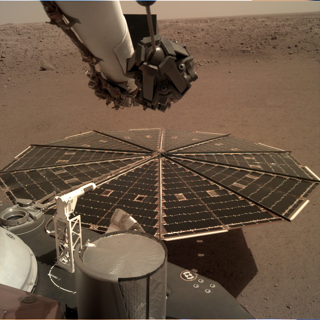 Round solar panel expanded over dusty red Martian plain.