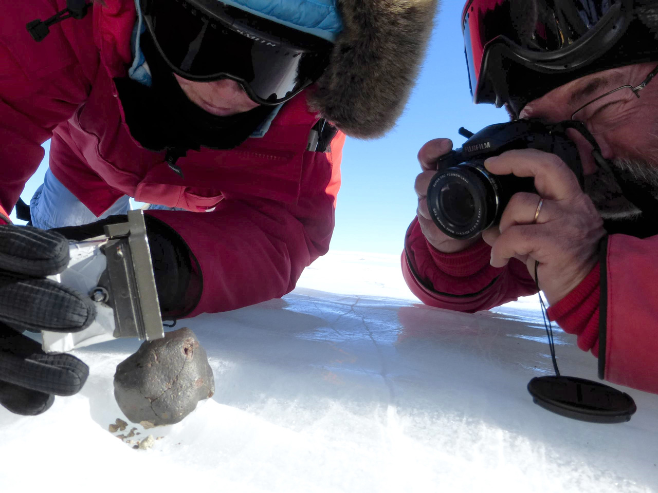 Two scientists examining a meteorite on snow-covered ground.