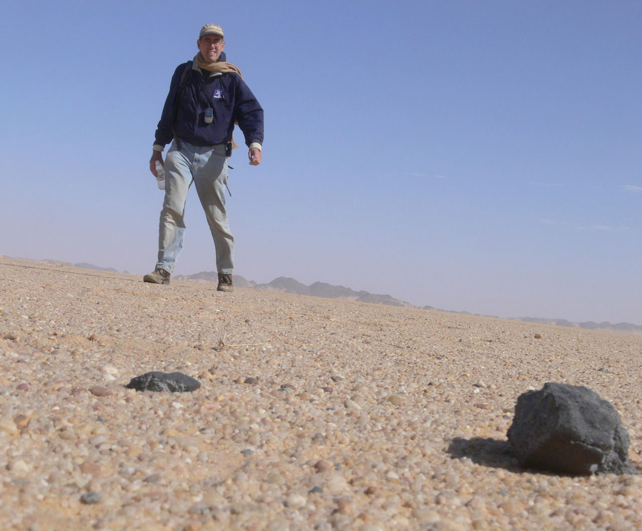 Man standing over small meteorite in desert sand.