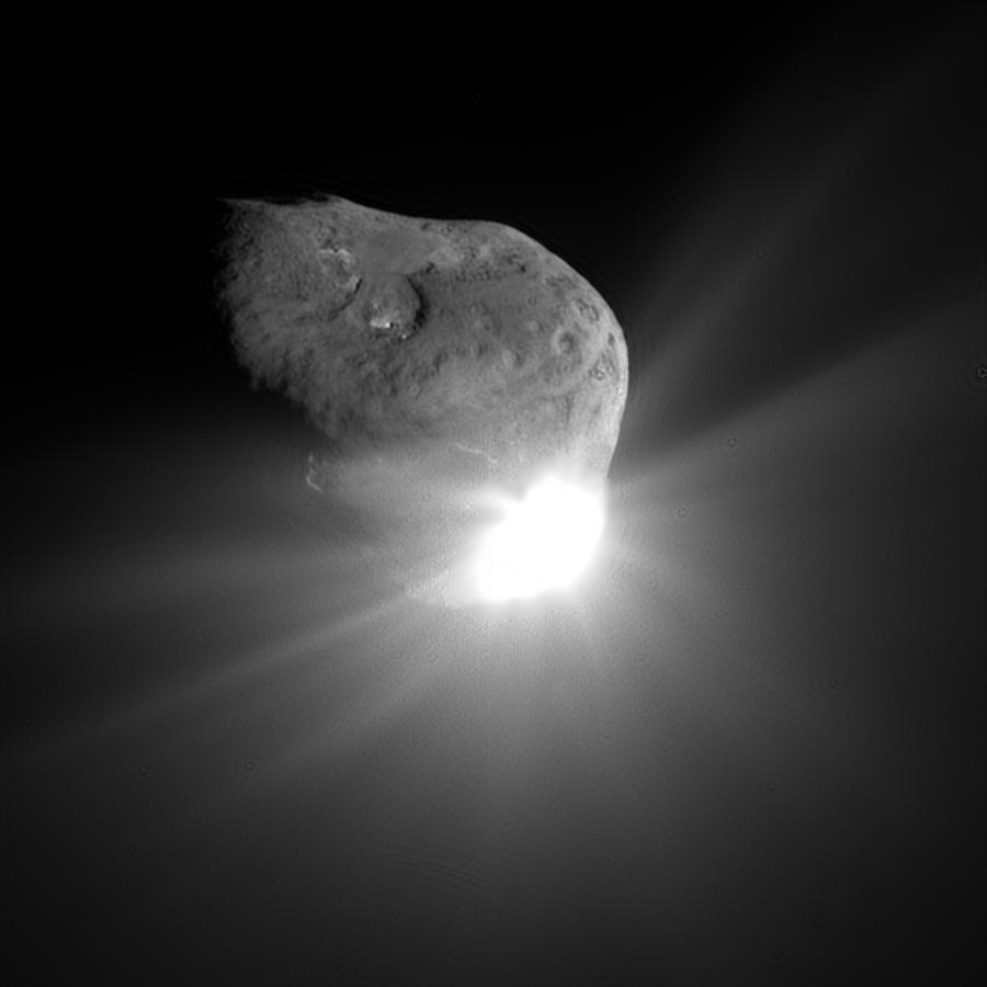 Comet nucleus illuminated by a bright flash of white light.