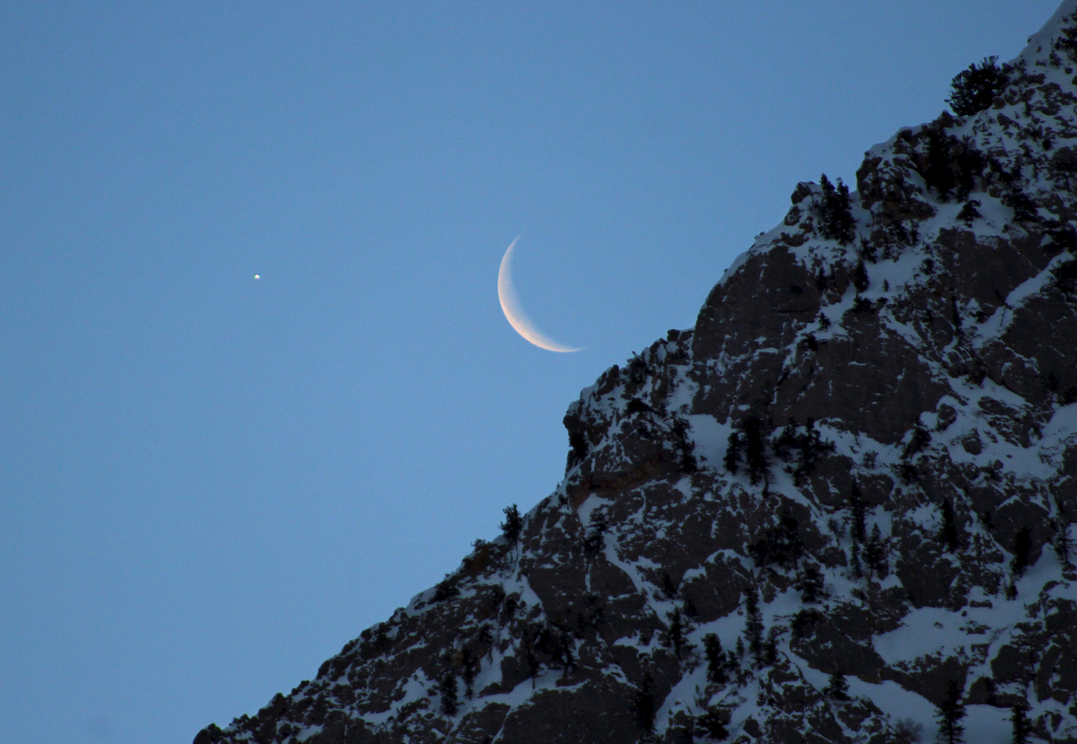 bright star and crescent moon above a rocky cliff