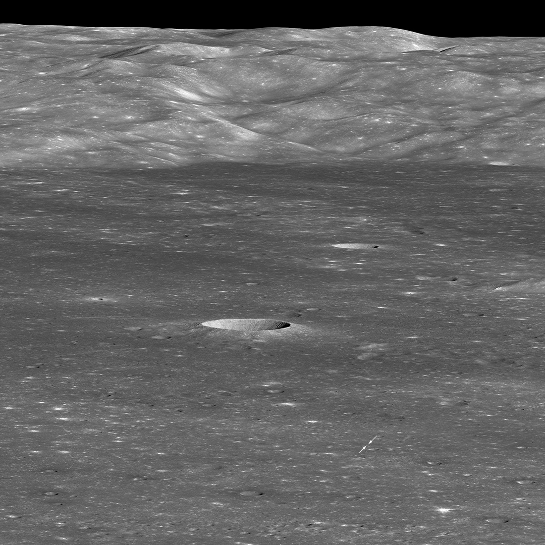 oblique view of large crater with arrows marking spot of landing