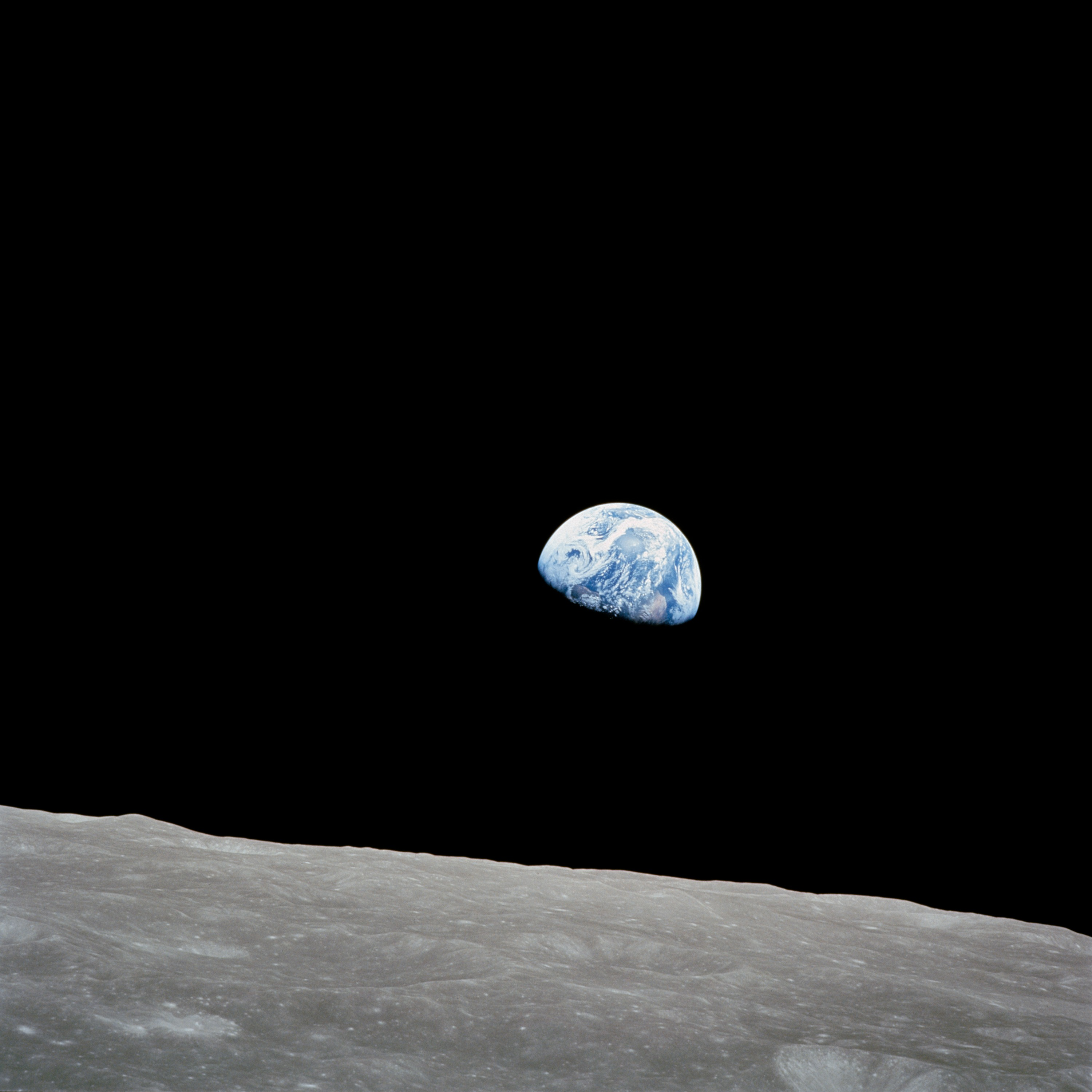 blue earth in black space above gray lunar surface