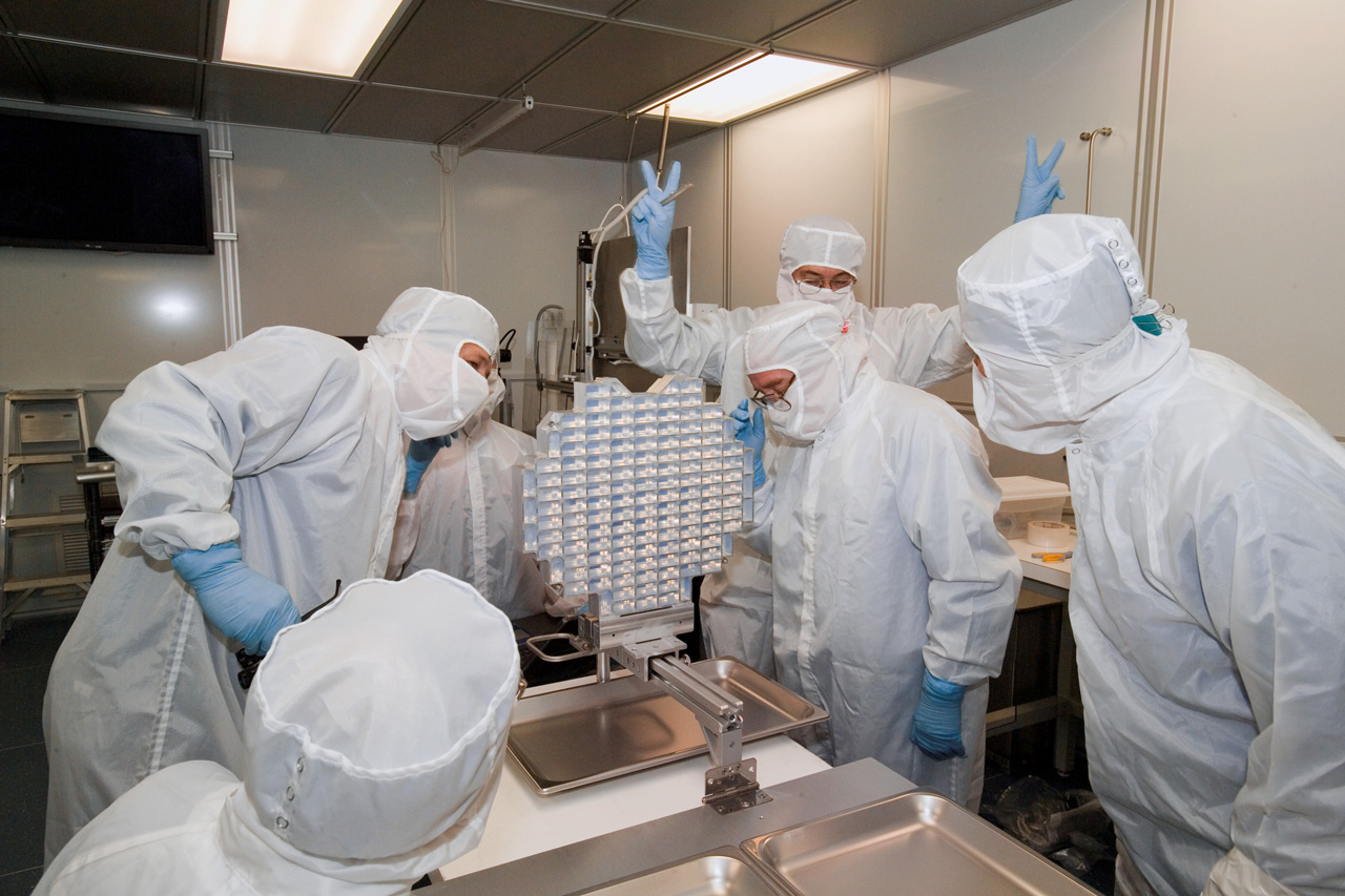 People in clean room celebrating with spacecraft instrument.