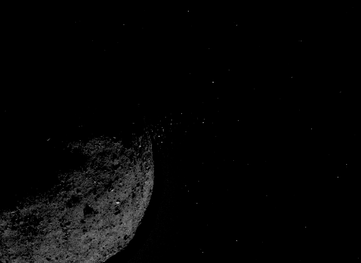 rocky asteroid ejecting small particles into space