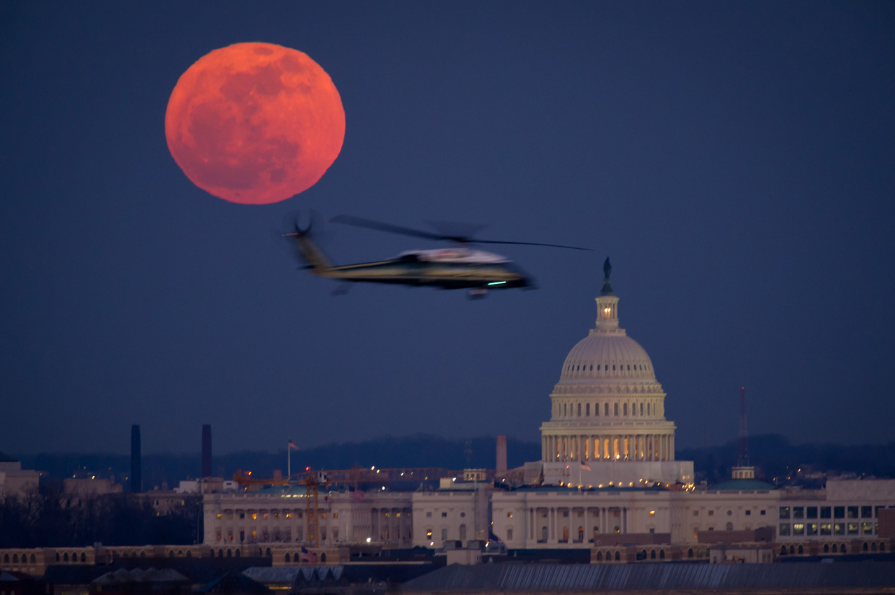 Helicopter flying past full moon and U.S. Capitol.