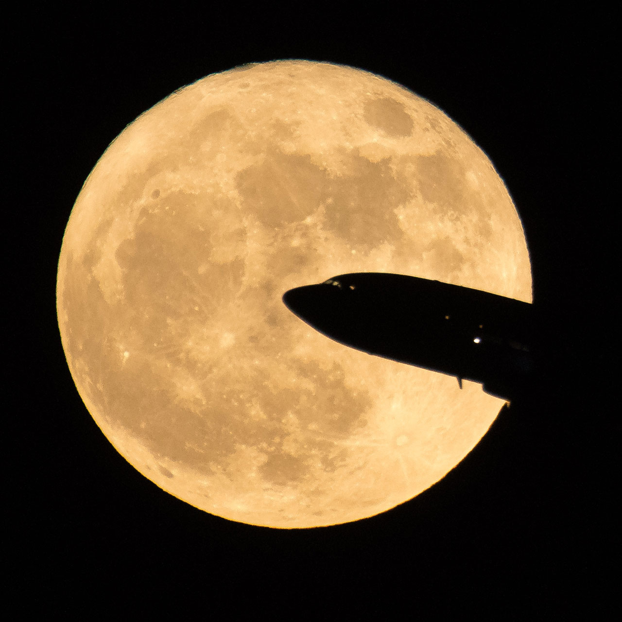 Airline silhouette in front of the Moon.