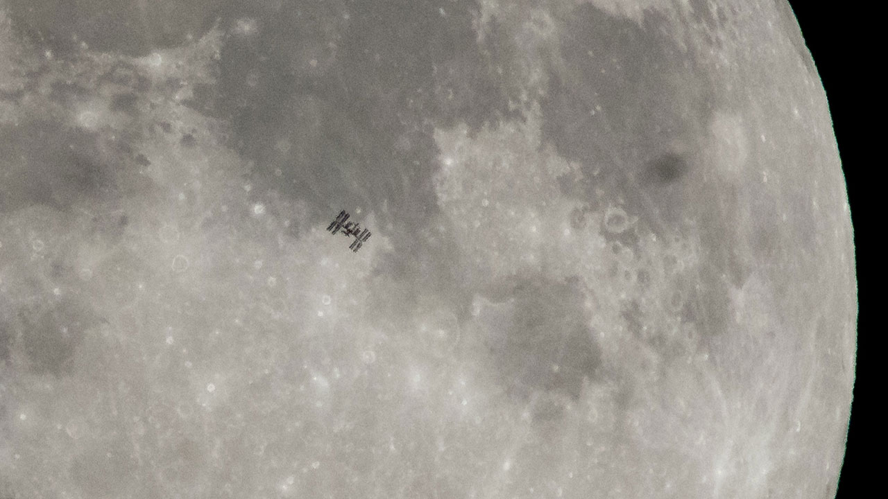 Space station seen in dark outline in front of the Moon.