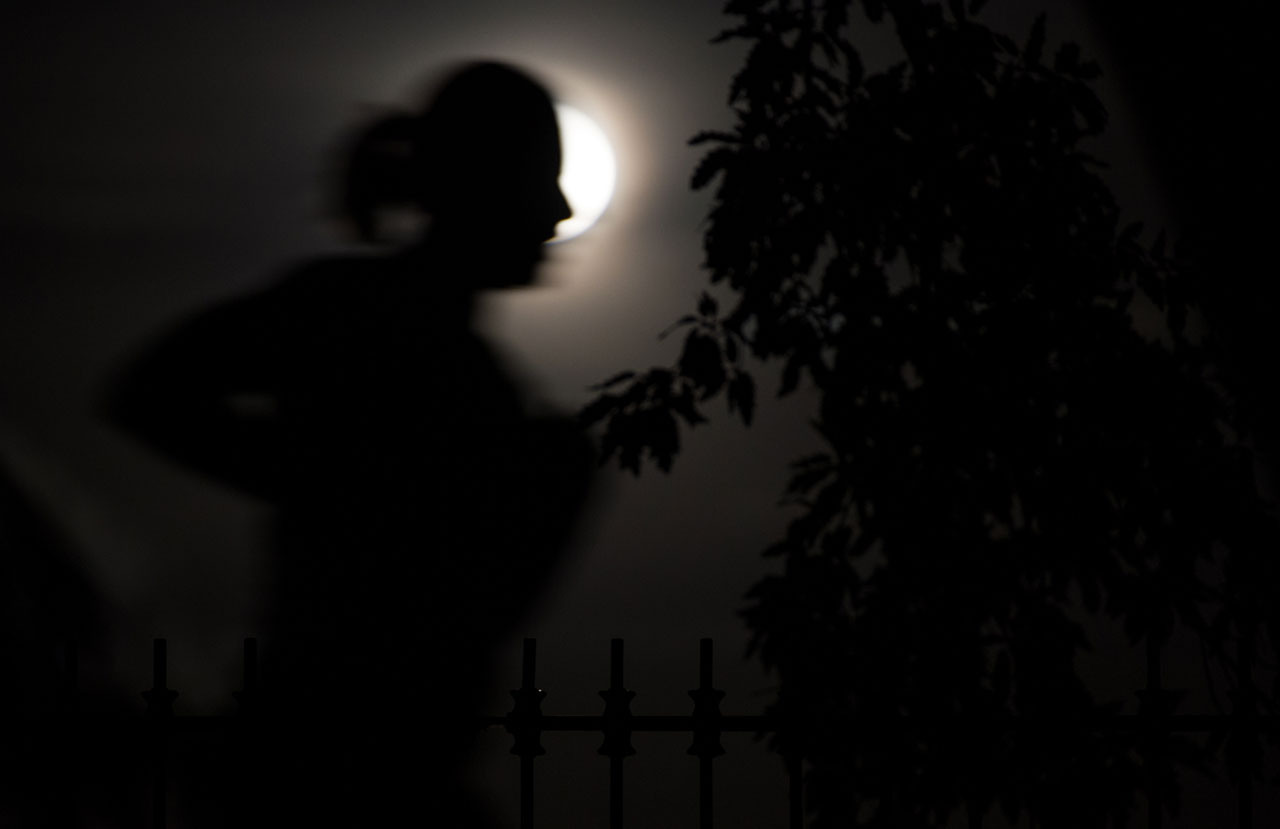 Jogger silhouetted in front of a full Moon.