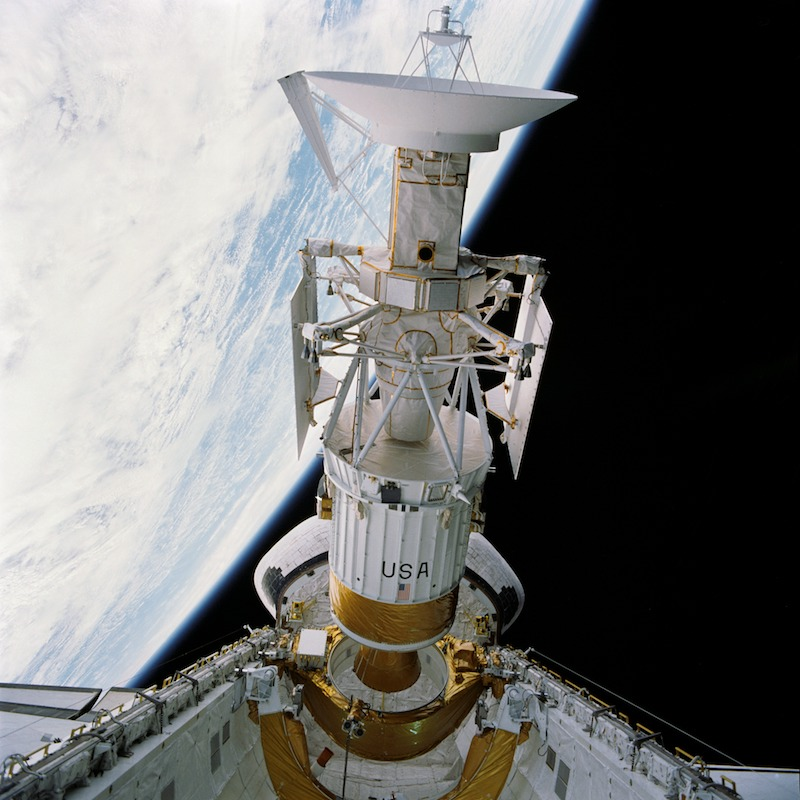 spacecraft leaving cargo bay of space shuttle with curving earth horizon in the background