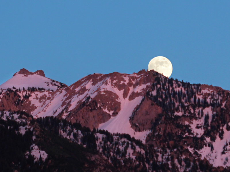 full moon over mountain ridge in pink sunset light