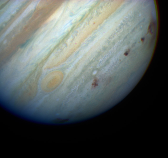 Jupiter with a line of dark impact marks along the bottom third of the planet.