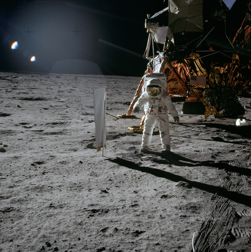 suited astronaut on lunar surface with spacecraft in background