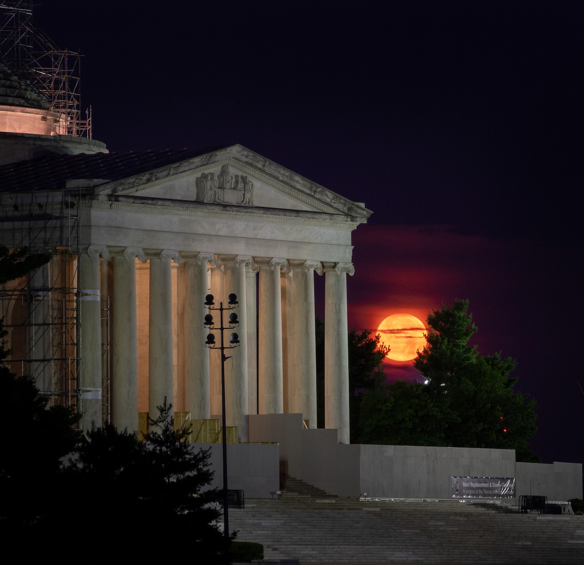 orange moon seen next to columned building