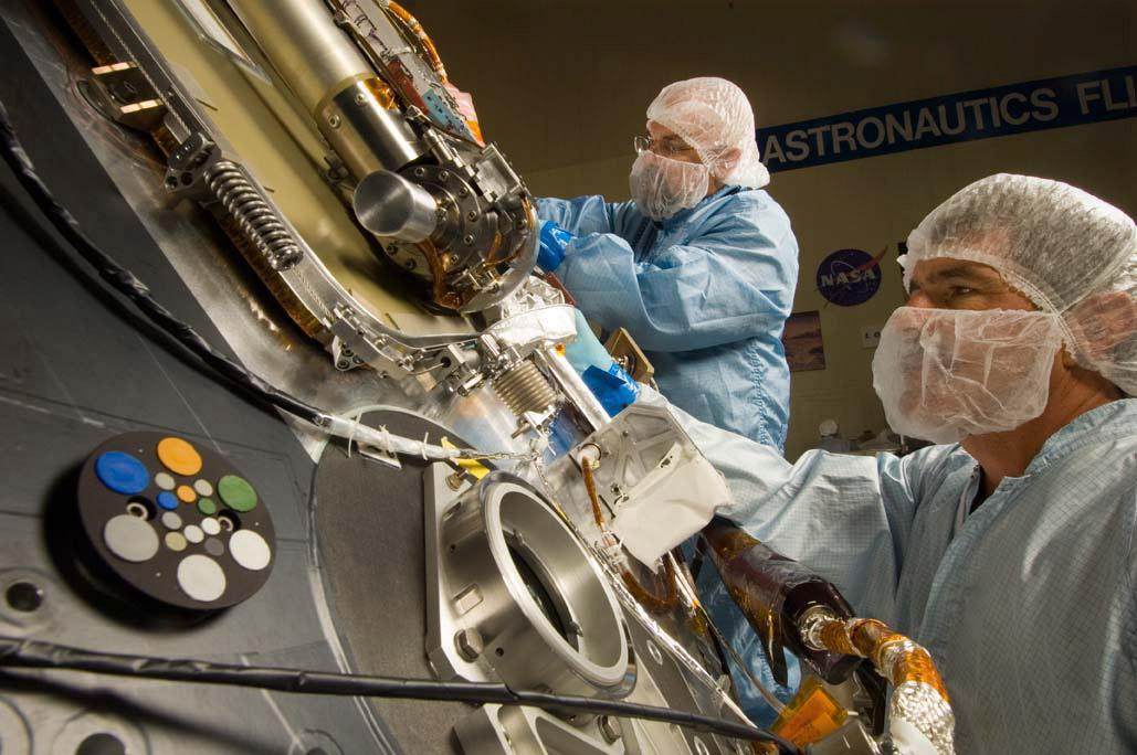 Lockheed Martin Space Systems technicians Jim Young (left) and Jack Farmerie (right) work on the science deck of NASA's Phoenix Mars Lander.