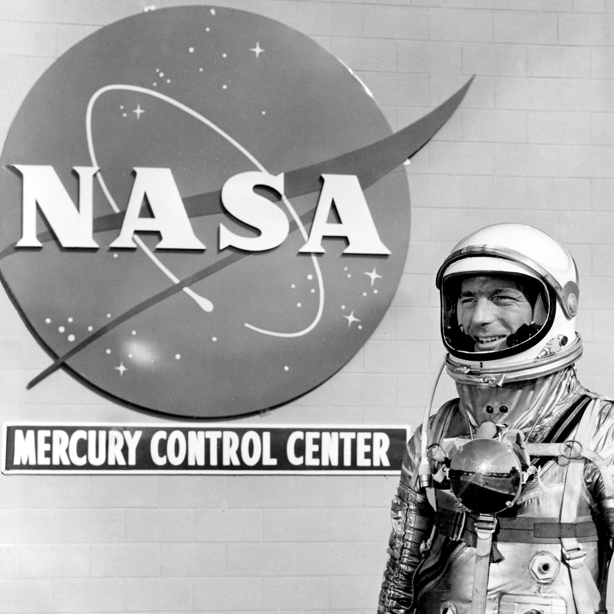 Mercury astronaut Scott Carpenter stands in front of the NASA insignia at Cape Canaveral.
