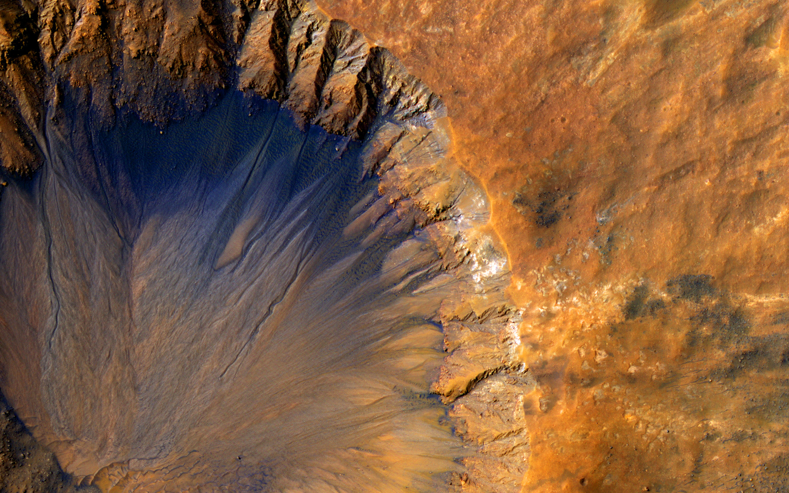 This impact crater appears relatively recent as it has a sharp rim and well-preserved ejecta, the material thrown out of the crater when a meteorite hit Mars.