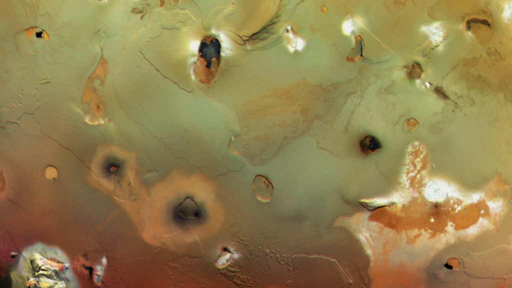 Collapsed volcanoes form large, dark spots on Io's surface.