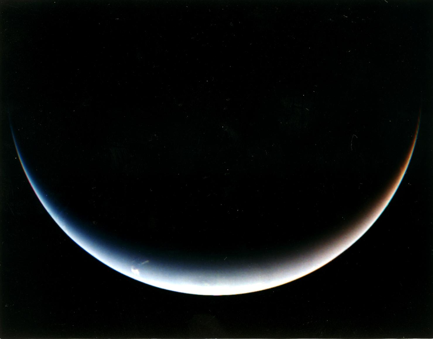 Voyager 2's post-encounter view of Neptune's south pole as the spacecraft sped away on a southward trajectory.