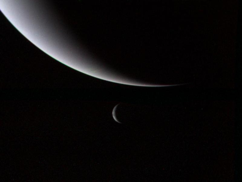 This dramatic view of the crescents of Neptune and Triton was acquired by Voyager 2 approximately 3 days, 6 and one-half hours after its closest approach to Neptune (north is to the right).