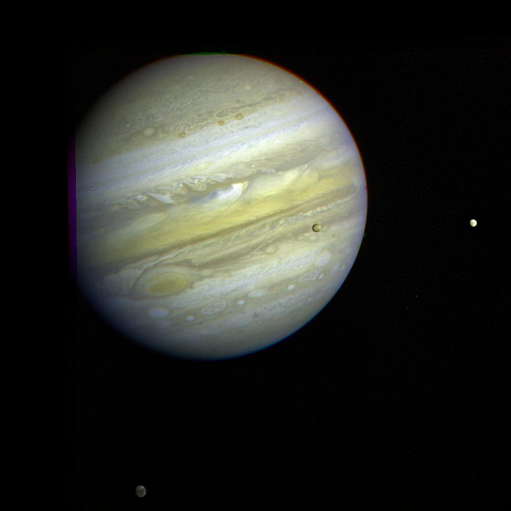 Jupiter, its Great Red Spot and three of its four largest satellites are visible in this photo taken Feb. 5, 1979, by Voyager 1.