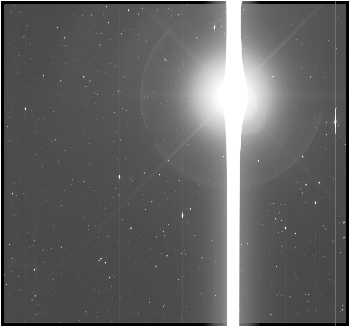 Black and white view of Earth as a bright lens flare against a background of stars.