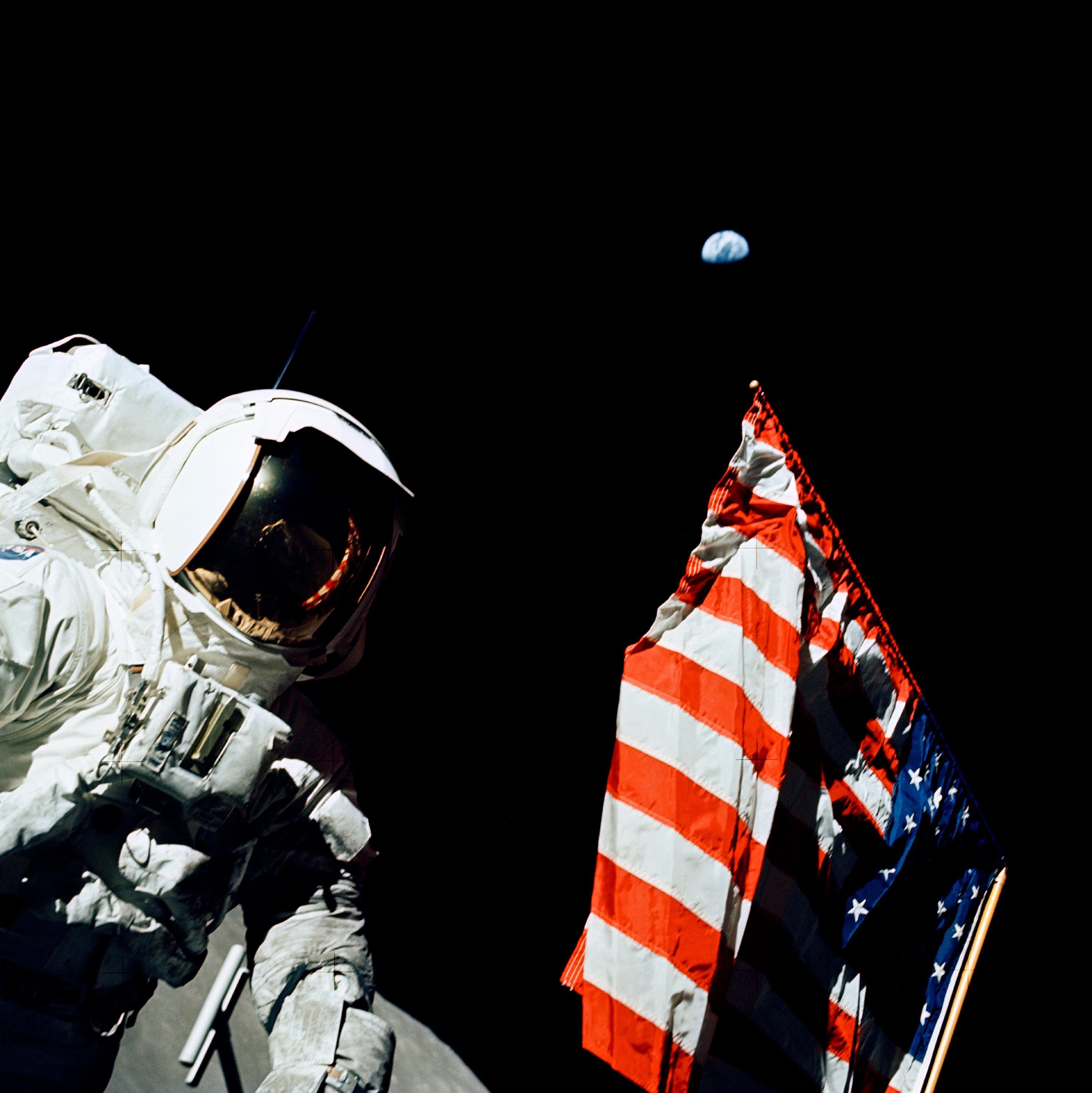 Photo of astronaut next to American flag with Earth in background