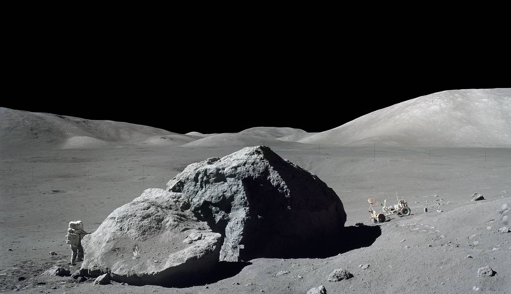 Astronaut on the moon with lunar boulder