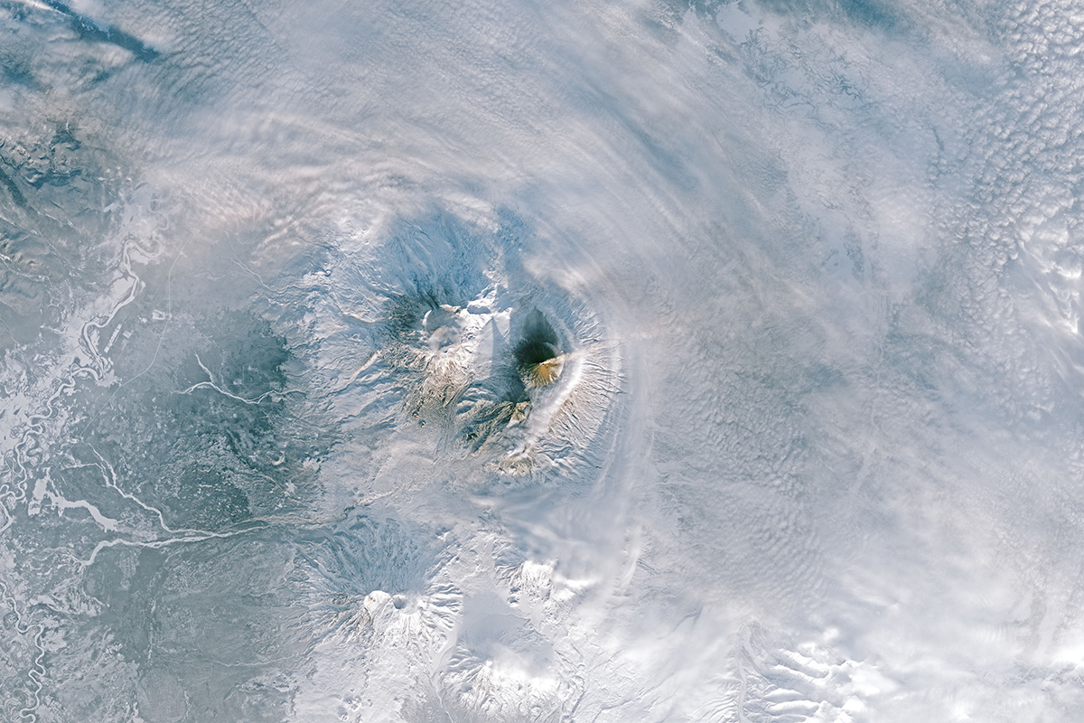 Aerial view of plumes rising over a volcano on a snow-covered landscape