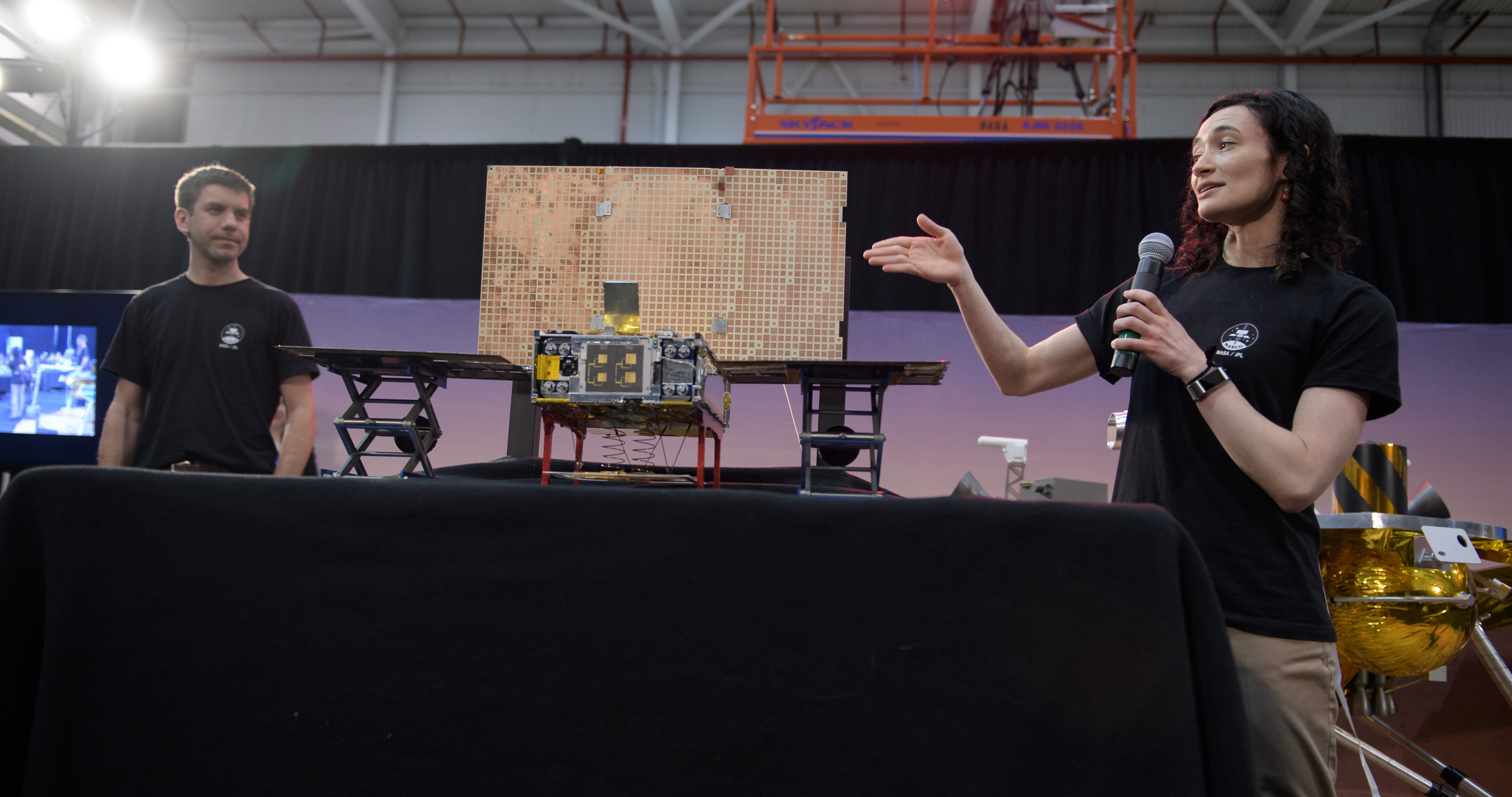 Man and woman standing next to MarCo cubesat.