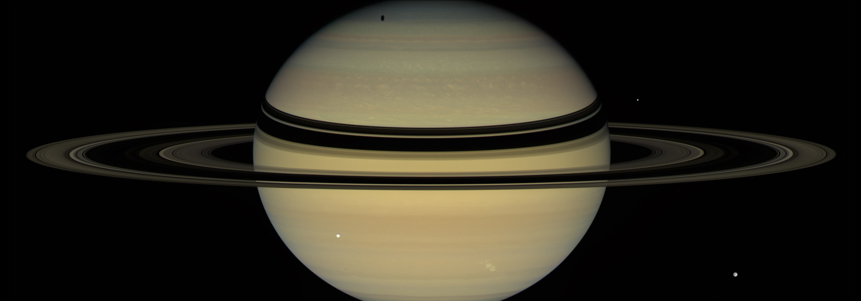 wide view of saturn and its rings with relatively smaller moons visible