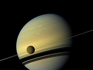 A giant of a moon appears before a giant of a planet undergoing seasonal changes in this natural color view of Titan and Saturn from NASA